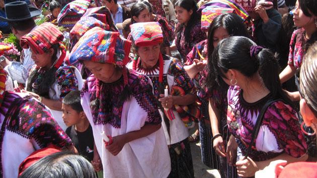 Esposas y otras mujeres dentro de la familia de los líderes de la <a href='#' title='Consejo de honor de líderes comunitarios y religiosos mayas, quienes interpretan los rituales católicos en términos de las creencias y la cosmovisión de los mayas.' class='glossary-tip'>Cofradía</a> siguen la procesión de su santo patrono. Las familias de la Cofradía sirven por un año, y tradicionalmente, durante este tiempo de servicio, otros miembros de la comunidad los ayudan a trabajar sus campos y sus cuidar casas.&nbsp;<span class='italic'>Crédito de imagen:&nbsp;Isabel Hawkins</span>