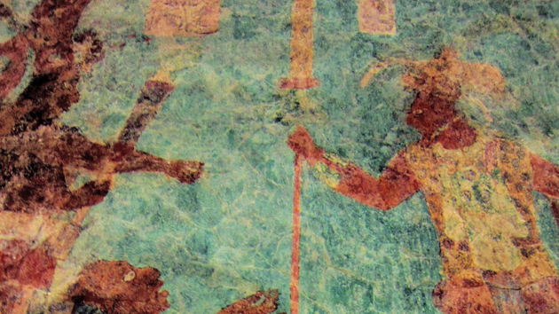 Room 2. This room depicts the greatest battle scene in Maya art. At least 100 figures were originally cast in this mural. King Chan Muwan appears on the upper right of this scene, his rigid posture mirrored by another victorious warrior on the upper left.&nbsp;<span class='italic'>Photo Credit:&nbsp;Isabel Hawkins</span>