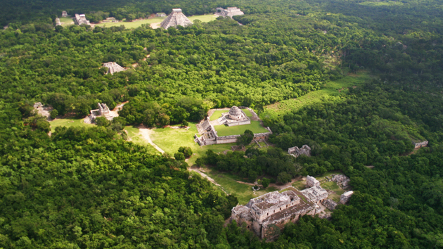 """Vista aérea de Chichén Itzá muestra el estilo <a href='#' class='glossary-tip' title=""""Significa """"montaña"""" en maya yucateco; una región al noroeste de la península de Yucatán. Un estilo arquitectónico caracterizado por una fina ornamentación."""">Puuc</a> en los edificios en el primer plano, el Observatorio en el centro y el Templo de <a href='#' class='glossary-tip' title=""""La serpiente emplumada de la mitología maya."""">Kukulkán</a> en el fondo. El Gran Juego de Pelota está a la izquierda de la pirámide y el Templo de los Guerreros está a la derecha.&nbsp;<span class='italic'>Crédito de imagen:&nbsp;Ideum/UC Regents</span>"""