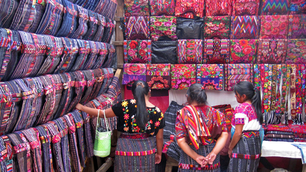 "In one of the myriad market stalls surrounding the church, young women inspect a wide selection of hand-woven <a href='#' class='glossary-tip' title=""The traditional dress of Maya women. In the Yucatán the huipil is a dress, while in Chiapas and Guatemala, the huipil is worn as a blouse."">huipiles</a>. The colors and designs, variations on traditional patterns, are evolving styles.&nbsp;<span class='italic'>Photo Credit:&nbsp;Isabel Hawkins</span>"