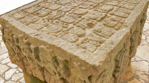 The original Altar Q found in the Acropolis now sits protected within the Sculpture Museum. The dynastic line of royal Copán is frozen on the four sides of this square altar. The portraits of 16 rulers are shown in historical order, each in full regalia and seated above the glyph that spells his name. The altar was commissioned by the last ruler, Yax Pasaj, in the year 776 CE.&nbsp;<span class='italic'>Photo Credit:&nbsp;Tepeu Roberto Poz Salanic</span>