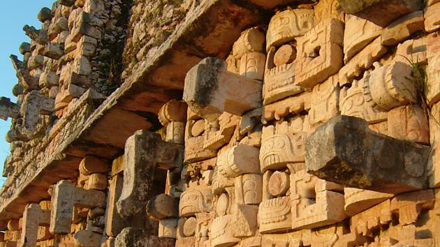 """Más de trecientas máscaras de <a href='#' class='glossary-tip' title=""""Deidad maya de la lluvia y el trueno."""">Chac</a> decoran el templo en el yacimiento arqueológico de Kabah. Esta ciudad está conectada a Uxmal por un <a href='#' class='glossary-tip' title=""""Significa """"camino blanco"""" en maya yucateco; un camino derecho elevado de origen prehispánico."""">sac be'</a> de 18 kilómetros (11 millas) de largo.&nbsp;<span class='italic'>Crédito de imagen:&nbsp;Isabel Hawkins</span>"""