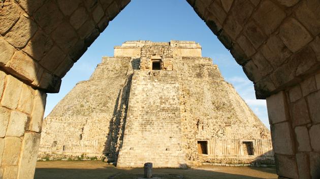 """La Pirámide del Adivino aparece en el fondo, vista a través del <a href='#' class='glossary-tip' title=""""El método clásico de los mayas de abarcar un espacio interior. Cargas de peso y vectores producen el ángulo y la altura de las bóvedas."""">arco maya corbelado</a>. Con más de 32 metros (150 pies) de alto, es la estructura más alta hecha por el hombre en la región <a href='#' class='glossary-tip' title=""""Significa """"montaña"""" en maya yucateco; una región al noroeste de la península de Yucatán. Un estilo arquitectónico caracterizado por una fina ornamentación."""">Puuc</a>. Representa los tres niveles cósmicos que unen el cielo, la Tierra y el <a href='#' class='glossary-tip' title=""""El mundo de nueve niveles subterráneos de los ancestros mayas y de las deidades tenebrosas. También conocido como Xibalbá."""">inframundo</a> y crea una relación explícita entre los dioses, los antepasados y humanos.&nbsp;<span class='italic'>Crédito de imagen:&nbsp;Ideum/UC Regents</span>"""