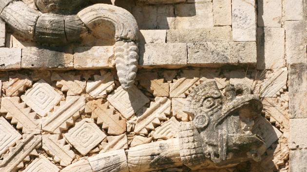 """La cabeza y cascabel de <a href='#' class='glossary-tip' title=""""La serpiente emplumada de la mitología maya."""">Kukulkán</a> (o <a href='#' class='glossary-tip' title=""""La serpiente emplumada de la mitología maya."""">Q'ukumatz</a>) están esculpidas en piedra sobre un fondo tallado que representa el cielo estrellado y el torbellino de <a href='#' class='glossary-tip' title=""""Deidad suprema en el mito de la creación de los mayas."""">Huracán</a>.&nbsp;<span class='italic'>Crédito de imagen:&nbsp;Ideum/UC Regents</span>"""