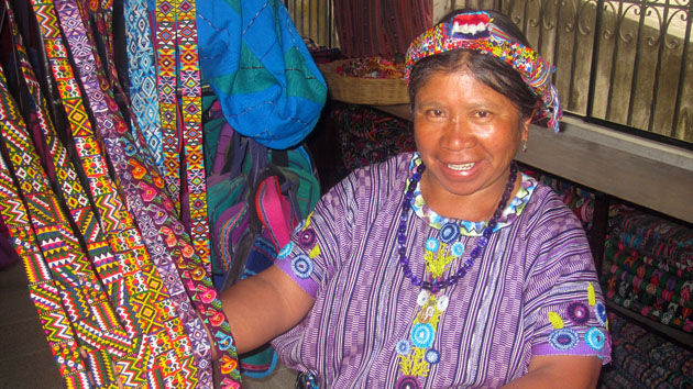 "A member of the Santa Ana textile cooperative shows off beautiful <a href='#' class='glossary-tip' title=""The Spanish word for ""ribbon,"" and a component of traditional Mayan clothing."">cintas</a>.&nbsp;<span class='italic'>Photo Credit:&nbsp;Isabel Hawkins</span>"