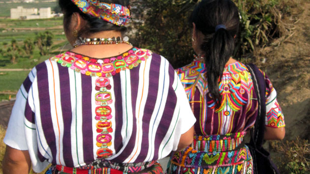 "Purple is the traditional color of the <a href='#' class='glossary-tip' title=""The traditional dress of Maya women. In the Yucatán the huipil is a dress, while in Chiapas and Guatemala, the huipil is worn as a blouse."">huipiles</a> from Zunil. More contemporary designs include the 20 days of the sacred Maya calendar, as seen here around the neck and on the back.&nbsp;<span class='italic'>Photo Credit:&nbsp;Isabel Hawkins</span>"