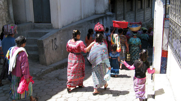 "Women of Zunil, wearing colorful <a href='#' class='glossary-tip' title=""The traditional dress of Maya women. In the Yucatán the huipil is a dress, while in Chiapas and Guatemala, the huipil is worn as a blouse."">huipiles</a>, walk towards the Santa Ana textile cooperative.&nbsp;<span class='italic'>Photo Credit:&nbsp;Luis Llovera Ramírez</span>"